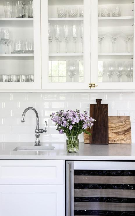 Antique brass Thomas O'Brien Bryant Sconces flank a beveled bathroom mirror  hung over white subway backsplash tiles lined with a chair rail