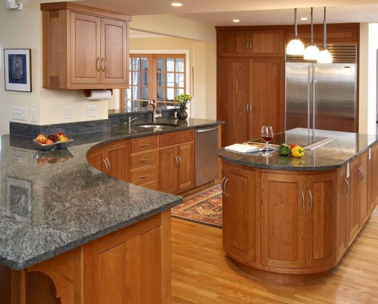 Rounded kitchen highlights light treated wooden cabinets with recessed  lighting over dark tile floor