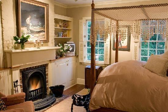 furniture styled vanity with sink top Cozy guest room with pale gold  walls, cherry sleigh bed with gold and beige bedding