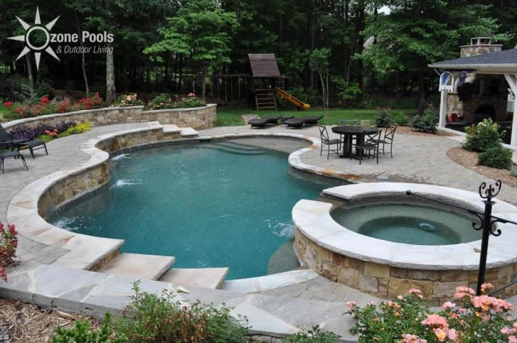 Beautiful pool with retaining wall with shrubs and acting as water falls