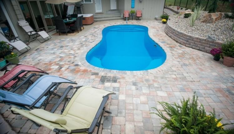 This backyard has a Cathedral fiberglass pool design by Thursday Pools