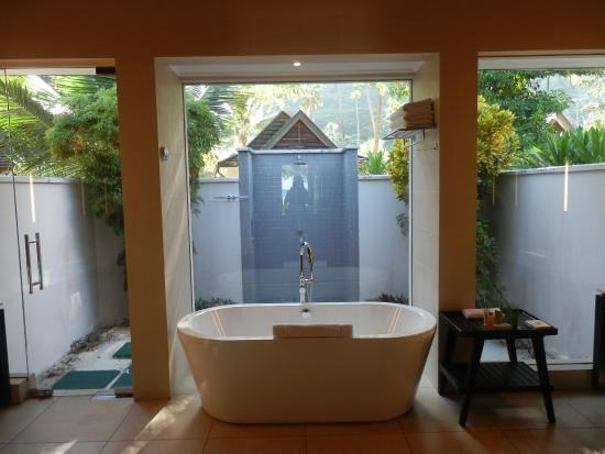 room and spacious bathroom, featuring a bathtub as well as indoor and outdoor  showers