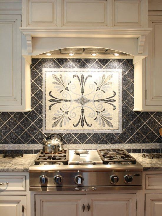 gray glass kitchen backsplash with carrera marble counters in a pretty  traditional white kitchen